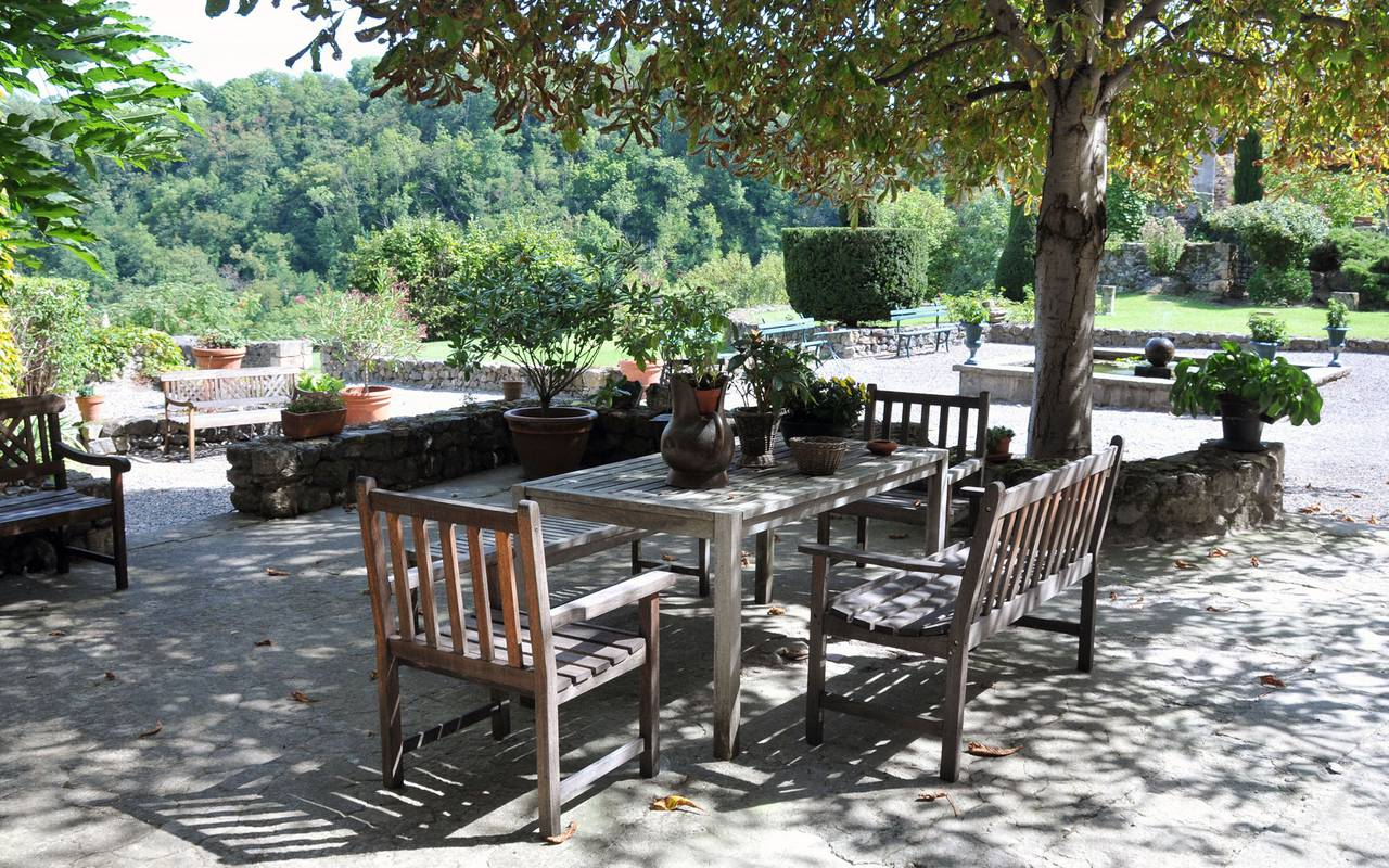 A table under the shadow of e tree on the terrace of the Château de Saint Saturnin, guest house Puy-de-Dôme